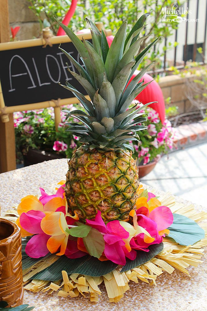 easiest luau centerpiece ever fresh pineapple and party decorations make the perfect centerpiece for your
