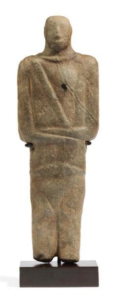 Grande statuette de personnage stylisé. Il est debout, les jambes jointes, les bras croisés sur l'abdomen, le gauche sur le droit. Le corps traité de façon géométrique est paré à la taille d'une ceinture,… - Pierre Bergé & associés - 01/06/2012