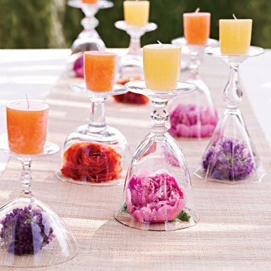 Turn stemware upside down, put votives on top, and tuck small blooms underneath or you could put any object there- photo, spools of tread, moss, etc..  Unique and elegant