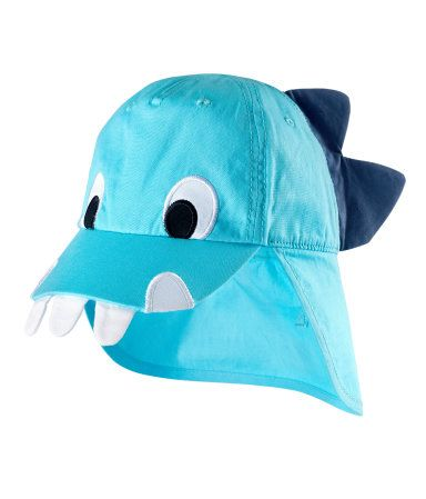 Cap with dragon applique, elasticized panel at back, and fold-up neck flap fastened in place with Velcro