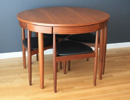 Hans Olsen Teak Dining Table with Chairs. This vintage Mid-Century Danish Modern dining set was designed by Hans Olsen for Frem Rojle in 1953. The four three-legged chairs nestle seamlessly in the side of the table. A set in good condition will run between $2800-4200 USD.