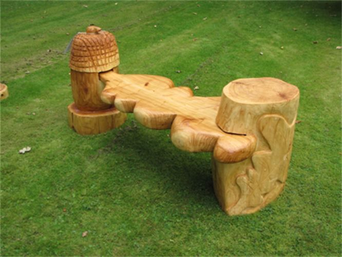 Garden Bench - approx 5 ft long -  £475.00  : shape of an oak leaf and an acorn for support, chainsaw carved from cedar wood and treated with Danish oil to preserve the wood