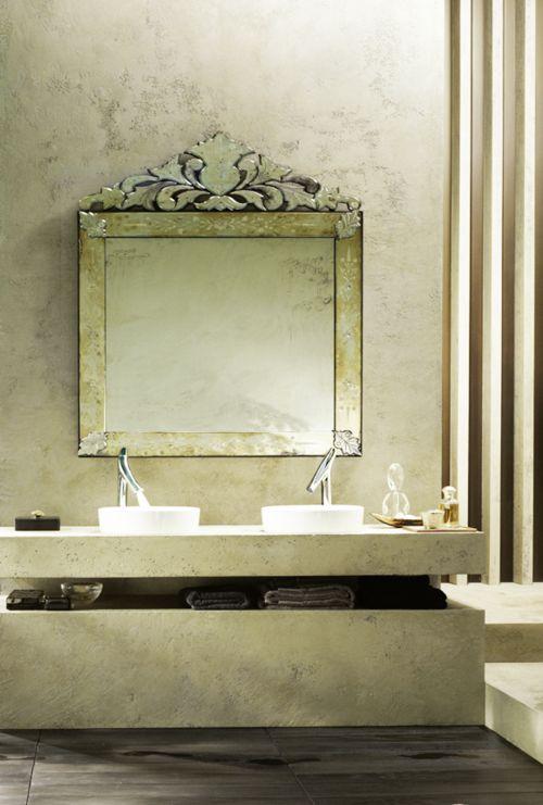 """This elegant Venetian mirror is the """"statement element""""  in an otherwise sleek yet minimalist modern bath."""