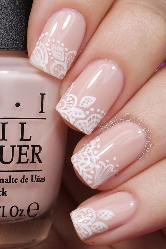 Floral inspired nude nail art. Give life to your nude nails by adding white polish on the tips with flower details on them.: