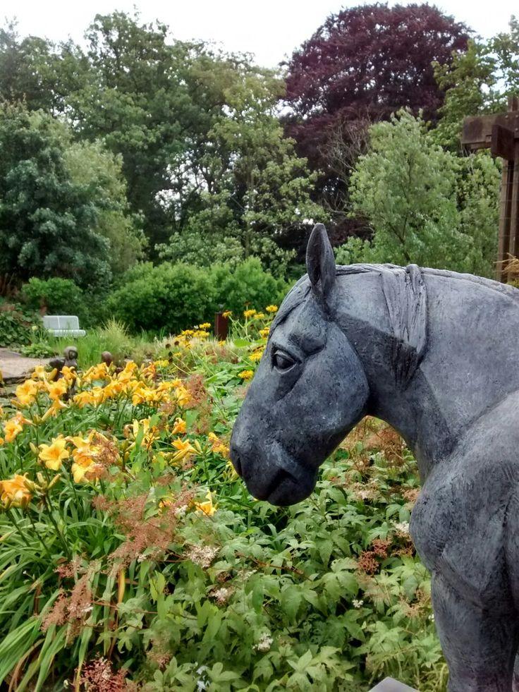Watertuin met op de voorgrond een deel van een beeld van Margriet Barends