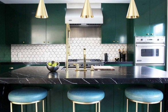Black marbled island, blue stools, gold faucets, gold hanging lights, green cupboards