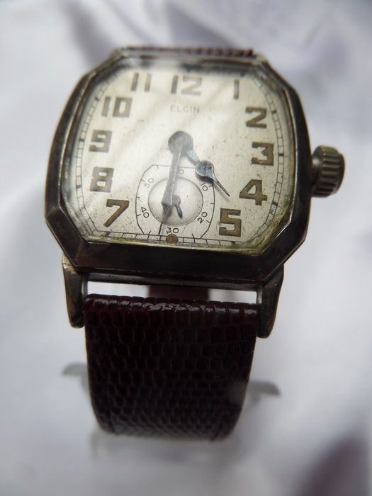 Elgin polshorloge 1927-15 jewels(Art Deco)-wit verguld  Gave polshorlogegroot modelvan het merk Elgin wat werkelijk unique is uit 1927(zie foto 36)Het horloge is nagezienloopt.Het wijzerblad is ongelooflijk schoonzonder krassen of beschadigingzilverkleurig.De Arabische cijfers zijn mooi zeegroen van kleur en volledig onbeschadigd.Op het wijzerblad staat Elgin.De kroon is orgineel.Mooie blauwe slalen wijzers.In tegenstelling met andere polshorloge's moet de opdraaiknop ingedrukt worden om op…