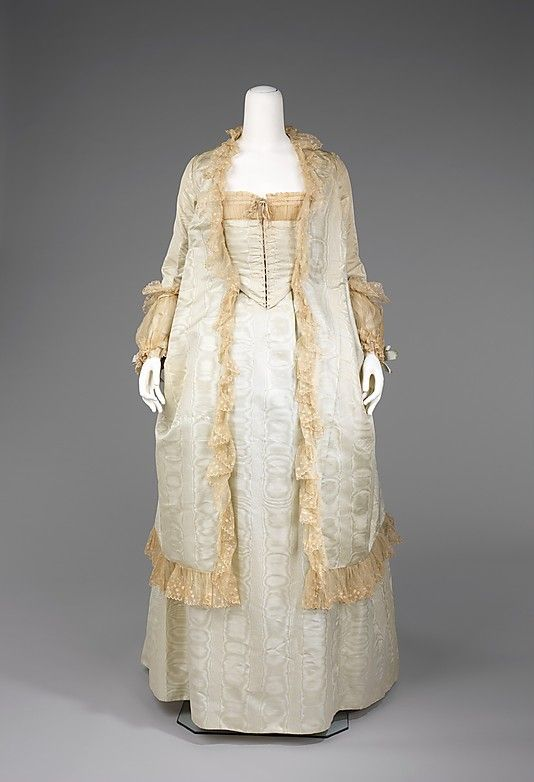 1880 Tea Gown  Culture: American  Medium: silk, cotton  The teagown was intended to be worn at home while greeting receiving people. As with most other 19th century garments it did not require the wearer to don a corset underneath. This level of comfort was only permissible in one's own home. An interesting construction aspect of this teagown is the back, which resembles a redingote and adds a masculine touch to a highly feminine garment.