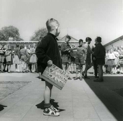 Jongetje met leesplank kijkt naar kinderen in de rij op het schoolplein. jaren 1950.