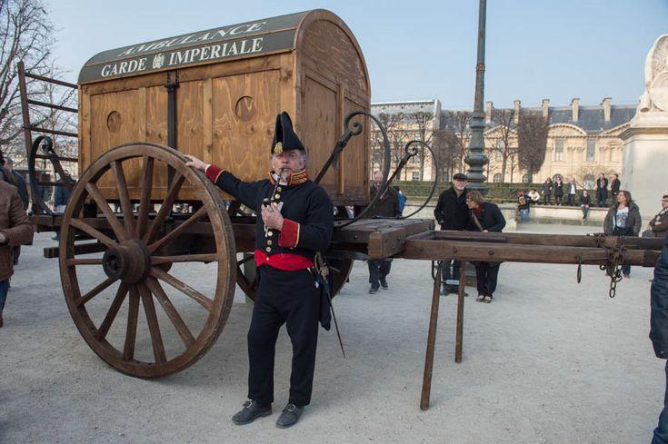 Un médecin militaire de l'Empire devant la reconstitution d'une ambulance volante. Celle-ci transportait le matériel nécessaire aux premiers gestes d'urgence.