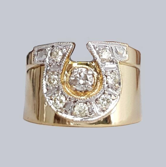Hoefijzer ring in 18 kt goud met diamanten van 044 ct-grootte: 17.8 mm 16/56 (EU)  Breed 18 kt geel gouden ring met centrale hoefijzer motief versierd door een centrale diamond omringd door zeven diamanten instellen in witgoud.Materiaal:Witgoud en geelgoud met gegarandeerde zuiverheid 18 kt (750/1000). Het hoeft niet een leesbaar keurmerk maar positief testten voor 18 kt goud met een toetssteen.Een briljante meten van ongeveer 3.2 mm met een geschatte totaalgewicht van 0.12 ct diamond…