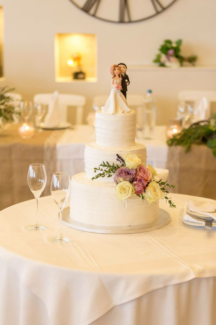 Three trier wedding cake,with frosting cream & flowers, cake topper stunts from couple, groom kept an ice cream and bride an espresso