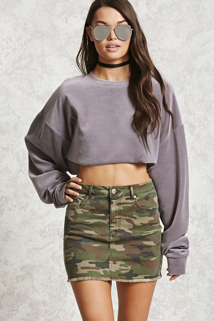 A mini denim skirt featuring allover camo print, a five-pocket construction, a zip fly, and a frayed hem.