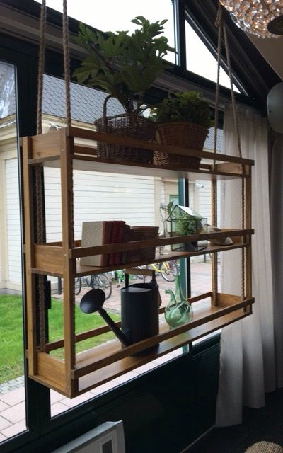 Amazing handmade custom shelf hung by ropes from the roof.