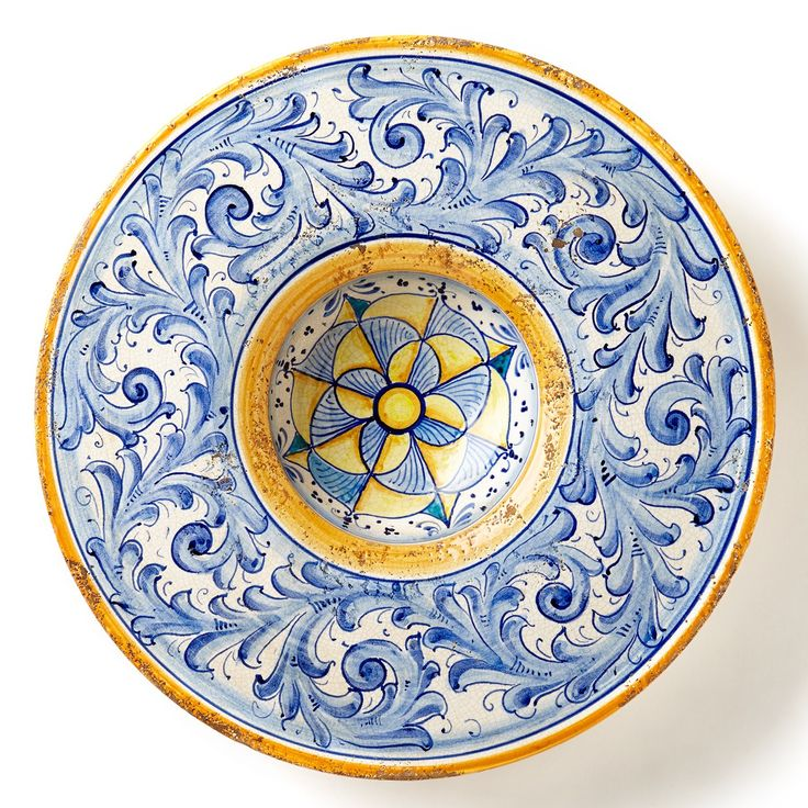The Flora Blu Large Round Wall Plate is an incredible work of art. With swirling designs reminiscent of the Italian Renaissance, the plate's strong, striking colors make a statement in your home.
