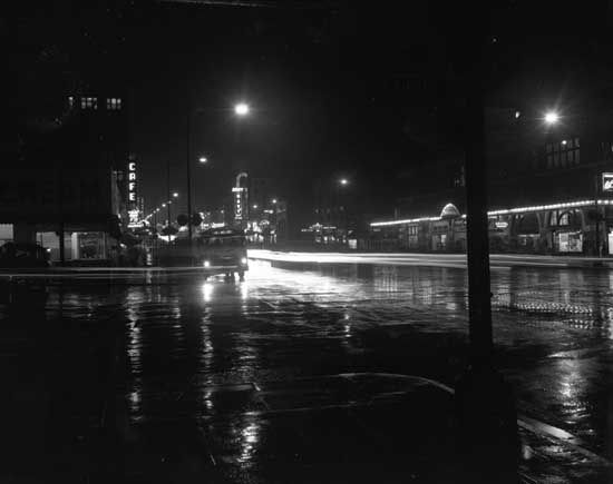 Photograph shows an artistic view of Columbia Street and Eighth Street at night with wet streets. Shows the BCER building and Army & Navy sign. [between 1949 and 1954]  IHP9267-0276