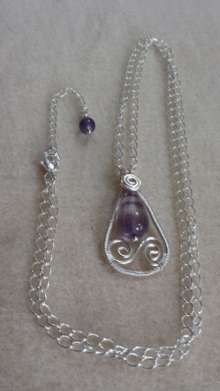 Hand crafted wire wrapped Silver plated pendant with Flurite drop and Spiral detail. Silver plated chain, Lobster claw clasp with extender chain