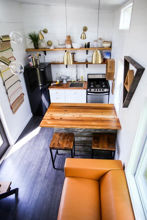 This 368 sq.ft. tiny house features a full kitchen with a beautiful reclaimed wood island that doubles as a table, a freestanding range, and apartment-size refrigerator.