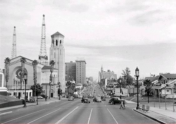 In this photo, we're looking east on Wilshire Blvd from Normandie Ave in 1947. We can see that back in the 40s, there were still homes on Wilshire Blvd. They're no longer there, of course, as is much of what we can see here. The church on the left is still around as is the Gaylord Apartment building farther down Wilshire. In between those two, we can see the dome of the original Brown Derby restaurant, which I wish was still around!