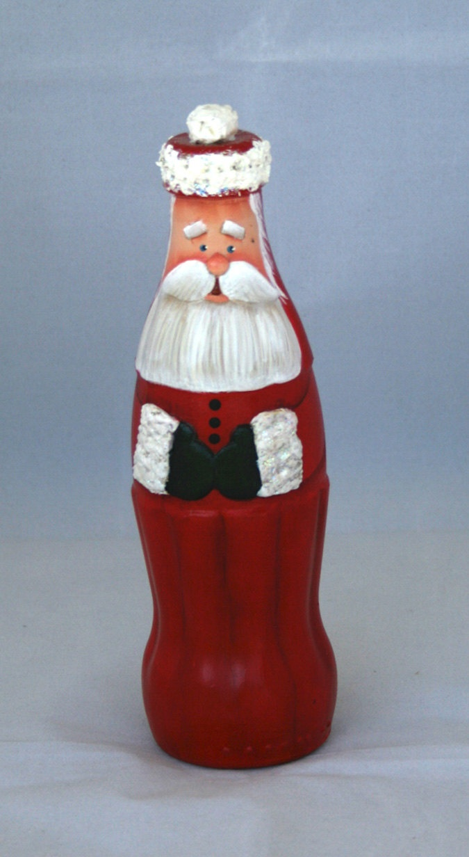 Santa made from a glass Coca Cola bottle embellished with clay, acrylic paint, and a little Snow-tex. Hiat is the bottle top with a little Snow-tex on top and a little glitter for some sparkle....