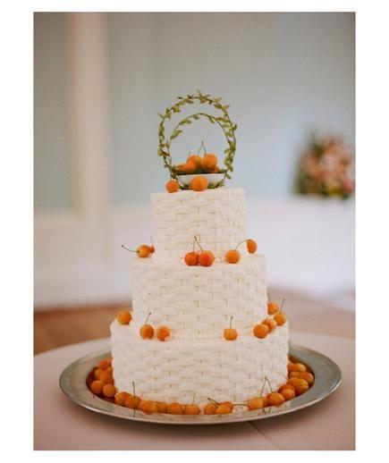 an elegant basketweave designed cake with cherries on top