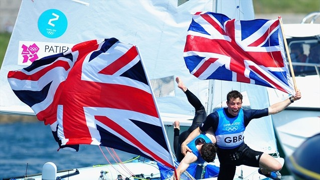 Luke Patience (L) and Stuart Bithell (R) of Great Britain celebrate finishing second and winning the silver medal in the Men's 470 Sailing on Day 14 of the London 2012 Olympic Games at the Weymouth & Portland Venue