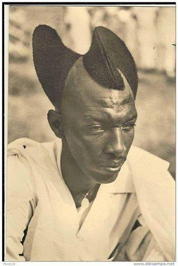"""From the Tutsi of Rwanda/Burundi. This hair design is called """"Amasunzu"""".  Amasunzu had more than 30 forms and was common among teenagers, the youth and, in some cases, adult men. The style is designed by cutting some of the hair sideways, towards the middle, then leave it to grow.  It was used by the Ancients, and is still used today."""