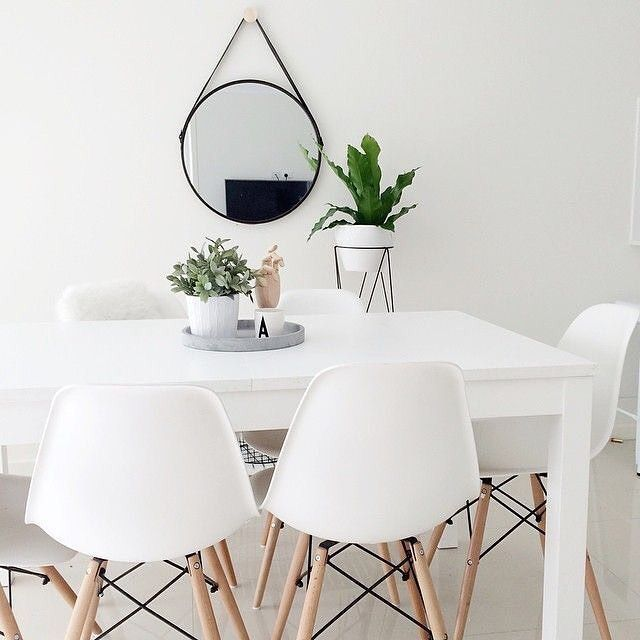 White eames chairs // round mirror // green plants