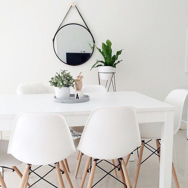 White eames chairs // round mirror // green plants