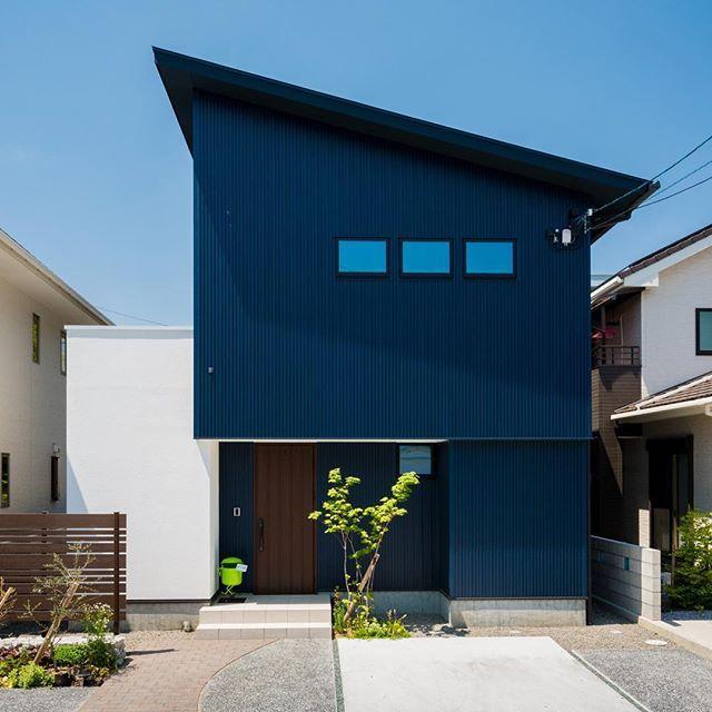 珍しいネイビーブルーのガルバリウムに 玄関の木製ドアが映えます