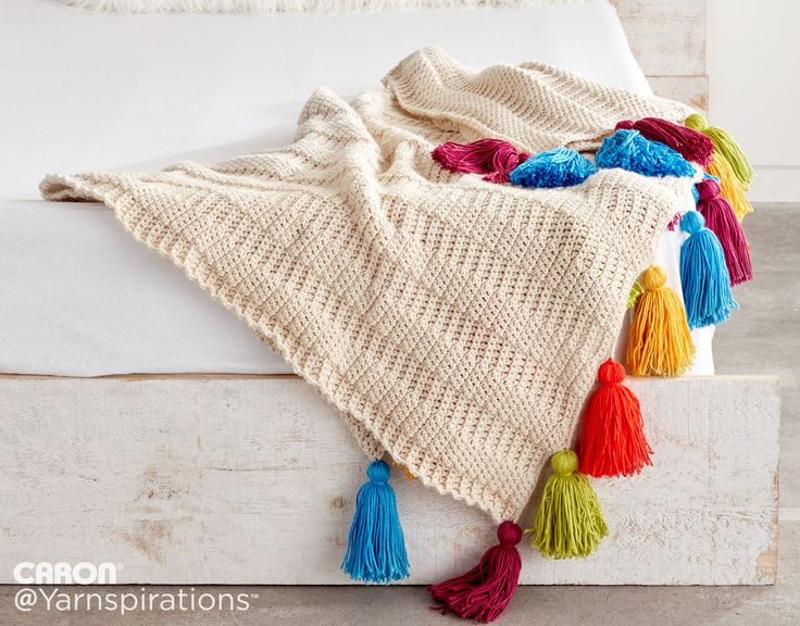 Caron Color: Crochet Tasseled Throw There's nothing better than making a simple afghan sparkle with the addition of some thick tassels! This little luxury elevates...