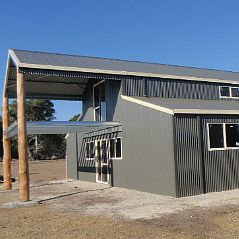 American barn with vertical cladding and 'bush' poles to the balcony.