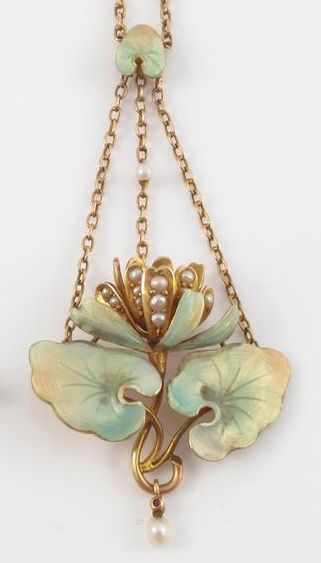 An Art Nouveau gold waterlily pendant decorated with shaded enamel and set with seed pearls. Stamped 15ct. 3.5cm wide. On a gold fine link chain.