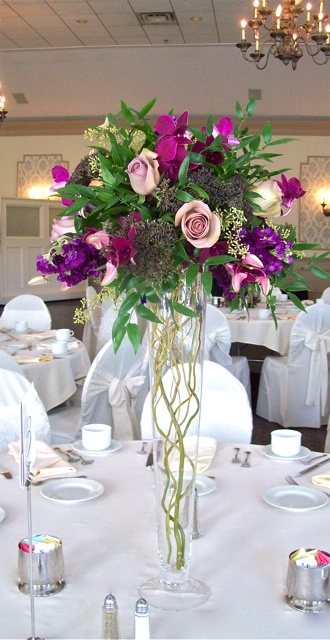 Tall Pilsner Centerpiece of antique purple roses with curly willow branches in the vase for Polo Fields Michigan Wedding