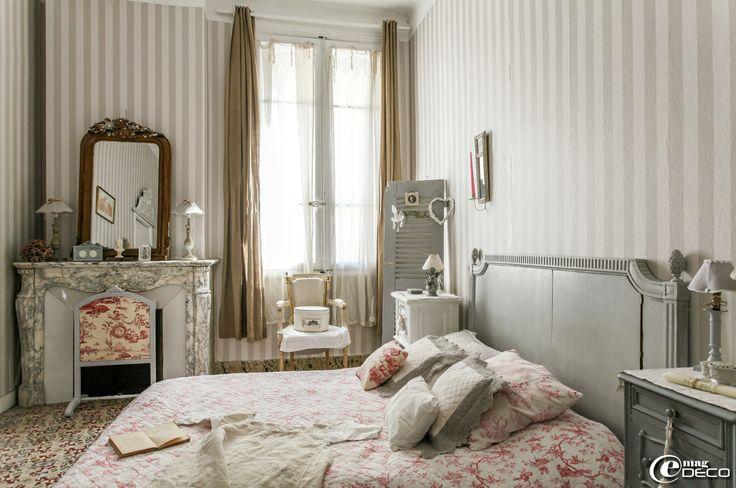 !  Dans une chambre, papier peint à rayures 'Castorama', boutis 'La Redoute' et coussins 'Sud étoffe', boîte à chapeaux 'Comptoir de Famille' posée sur un cabriolet de style Louis XVI retapissé de lin naturel 'Sur un air Gustavien'