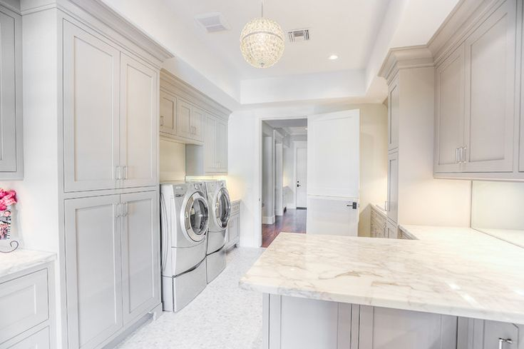 White and gray laundry room features gray cabinets accented with gray moldings paired with white and gray marble countertops and mirrored backsplash. A beaded globe chandelier illuminates gray front-load washer and dryer flanked by gray shaker cabinets atop mosaic marble tiled floor.