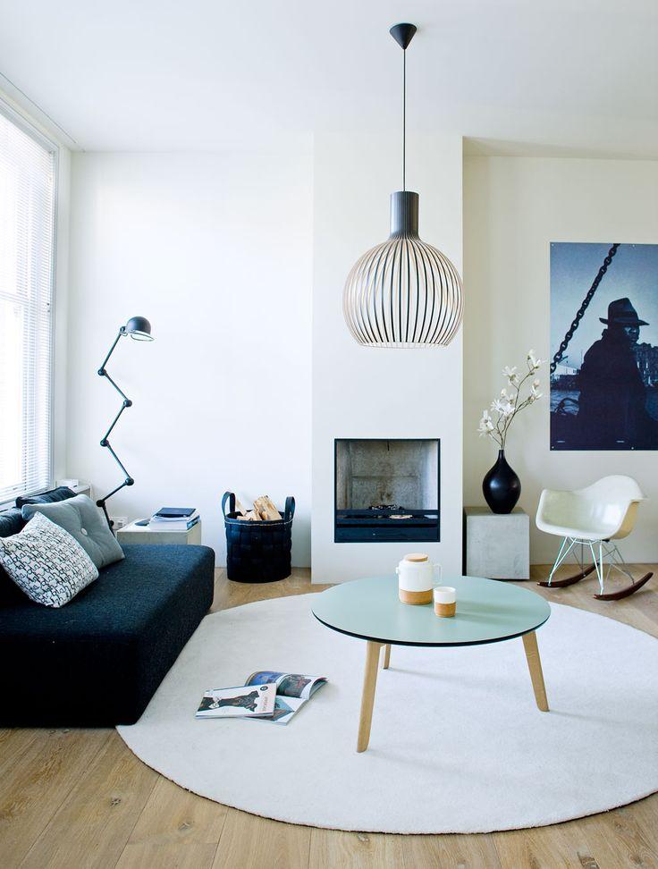 Mooie vorm van de zwarte vaas en lamp boven salontafel (http://www.weidesign.nl/produkten/616/secto-design-octo-4240-wit)