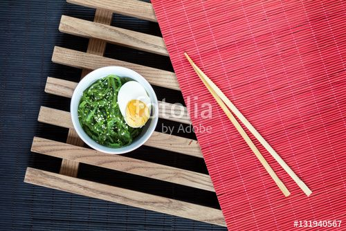 """Download the royalty-free photo """"Hiyashi wakame with sesame and nut sauce, boiled egg in ceramic bowl and bran bread on the rustic wooden lattice, black and red makisu"""" created by Victoria Kondysenko at the lowest price on Fotolia.com. Browse our cheap image bank online to find the perfect stock photo for your marketing projects!"""