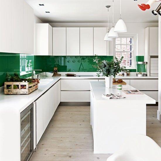 Une maison londonienne qui aime l'art : cuisine moderne blanche et crédence verte.