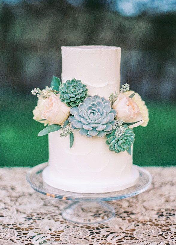 A simple two-tiered white wedding cake with fresh flowers and succulents. Rustic Cream & Blush Arizona Wedding