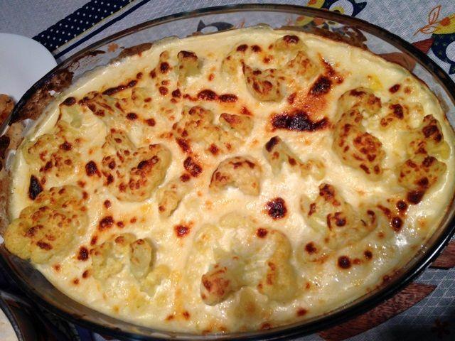 Receita de Couve-flor gratinada2 xícaras de leite 2 colheres de sopa de manteiga 2 colheres de sopa de trigo dissolvida em um pouco de leite Sal a gosto 1 dente de alho amassado 150 g de mussarela picada ou ralada 150 g de presunto picado ou ralado 1 caixinha de creme de leite Queijo parmesão ralado 1 couve-flor pequena 1 pitada de sal 2 pacotinhos de sazón amarelo (pode ser qualquer tempero) .