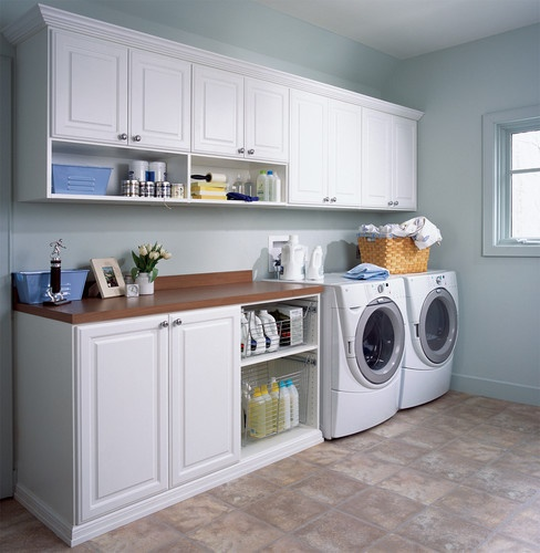 his bright laundry room unit in white melamine provides a well appointed place to work. The area includes a chrome valet rod for hanging or drip drying, a 1½ inch mica counter top for folding clothes, chrome pull-out baskets for sorting, open shelving for frequently used supplies and traditional raised panel drawers and cabinets with crown molding for hidden storage