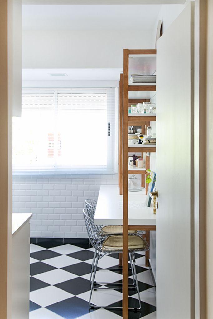 Cocina con piso tipo damero. Revestimiento en paredes tipo subway tile biselado blanco. Mueble de guardado y comedor diario en laca blanca y lenga con lustre mate. Sillas bertoia.