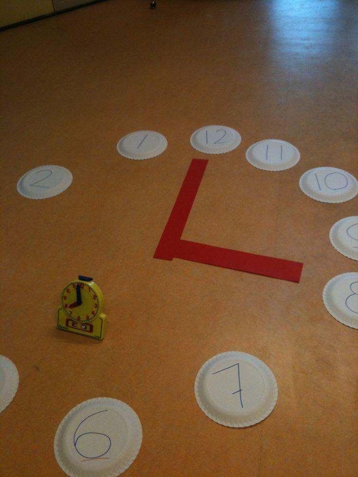 Maak de klok van papieren bordjes met wijzers en de hele uren