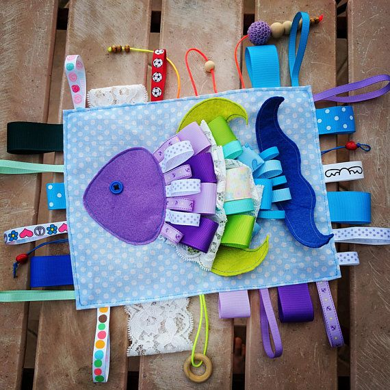 Little babes will love to touch this with their little fingers. The size of the book is 21*17 cm (8* 6 inches) without the ribbons. Personalize it with a stitched name with wood button. The toy develops: -fine motor skills -gumption -spatial imagination -attention -mathematical and creative skills -diligence This sensory toy is made to order. So if you would like any adaptations (wood ring, bells...), please ask me about it :). Just let me know! This makes a lovely gift for any newborn ba...