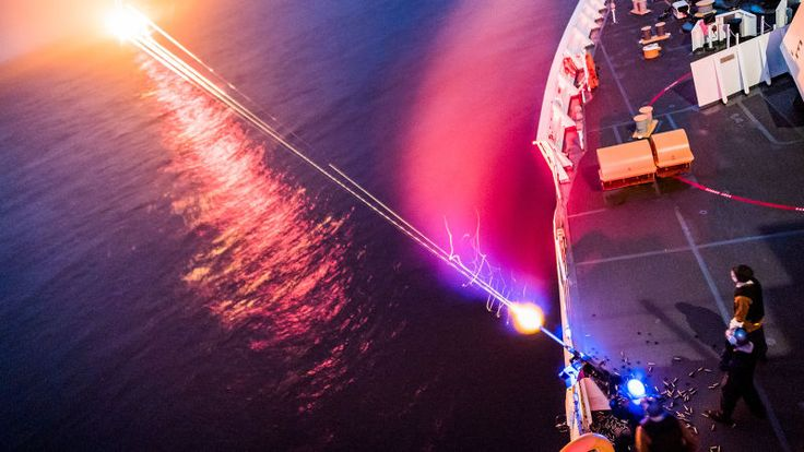 Long exposure shots always make nighttime scenes look futuristic. This isn't a frame from a science fiction movie, then, but rather U.S. Coast Guard members shooting a 50 caliber machine gun at night aboard Coast Guard Cutter Stratton.