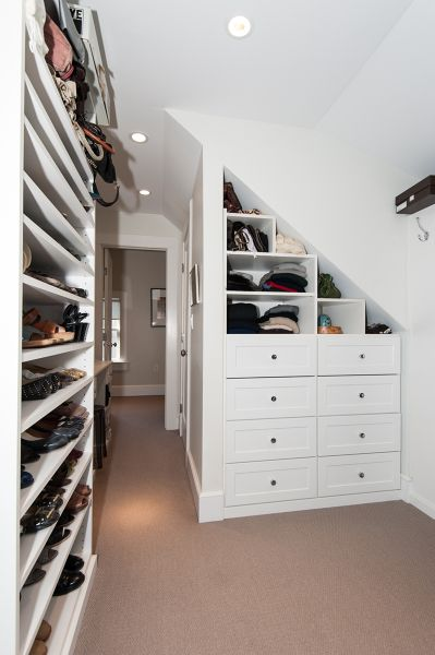 Shelves under slope are good style for loft closet storage.