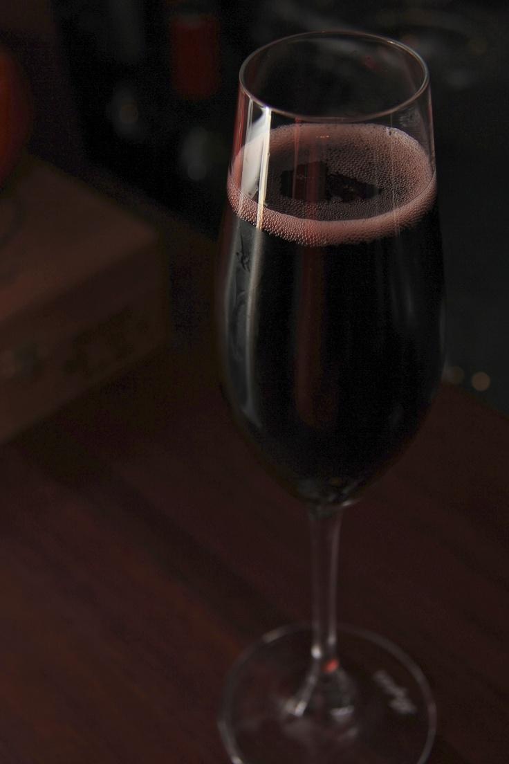 Wine glasses.  A glass of Sparkling Red Wine from Milvine Estate in Heathcote Australia. So dark yet so lively.