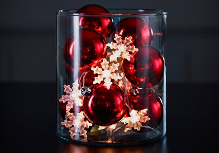 string of lights and ornaments in a vase