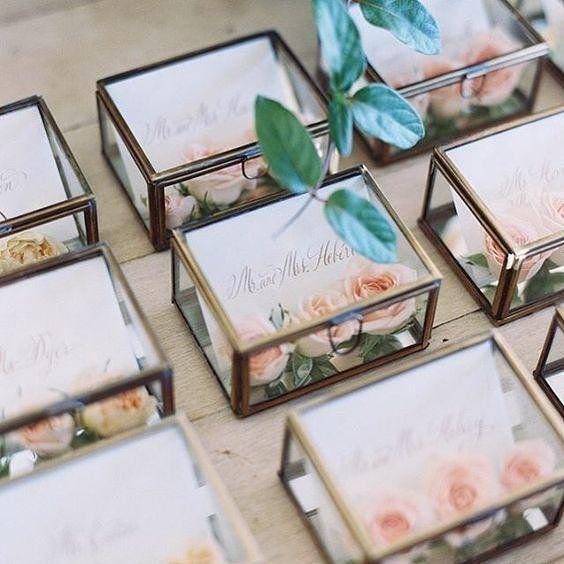 """Um jeito original de """"escort cards"""" (cartões de escolta): uma caixinha de jóia! #⃣1⃣ Cada uma delas vem com o nome do convidado e o número da mesa que ele deve sentar, acompanhada de três lindos botões de rosas. Além de indicar o local do assento, a caixinha serve de lembrancinha para levar ao final do casamento.  Muito criativa e linda essa ideia!  {via @atodoconfetti Instagram} #caixadejoia #cartõesdeescolta #lembranca #lembrancadecasamento #lembrancinha #casamento #inspiracaocasament..."""